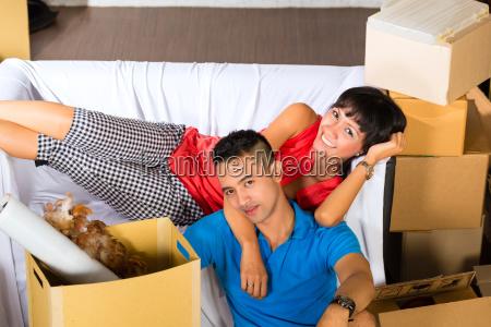 asian couple having break while moving