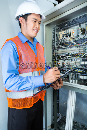 asian electrician at panel on construction