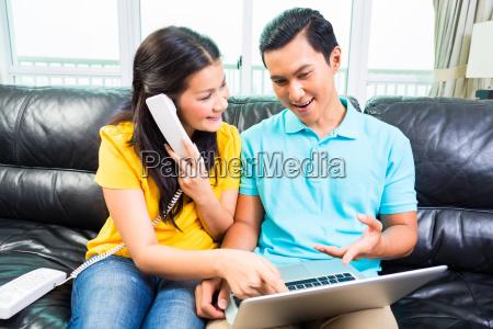 asian couple calling costumer hotline