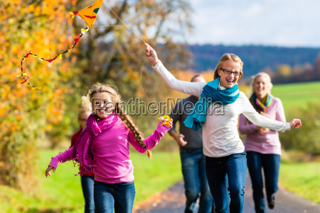 family take walk in autumn forest