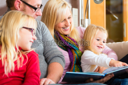 family reading story in book on