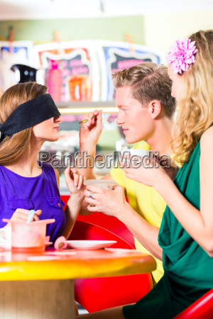 friends tasting ice cream in cafe