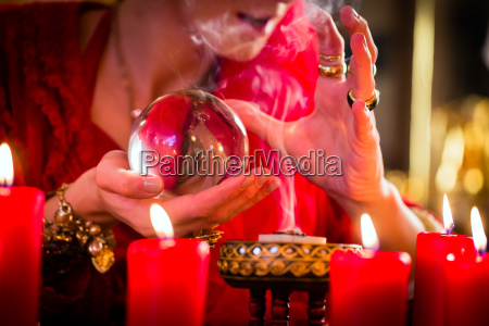 soothsayer in seance with crystal ball