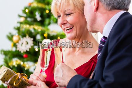 senior couple celebrating christmas with champagne