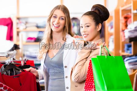 women buying fashion in shop or