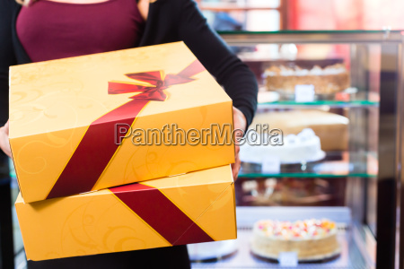 woman presenting takeaway boxes of confectionery