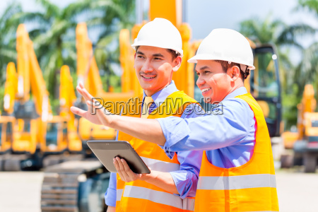 asian engineer discussing plans on construction