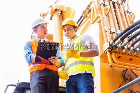 asian mechanic with construction machine