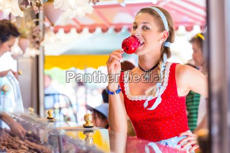 woman eating candy apple at oktoberfest