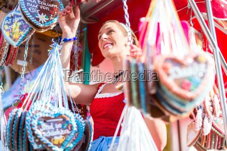woman buying gingerbread heart at oktoberfest