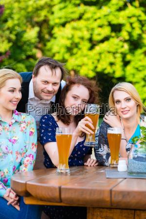 friends sitting in beer garden restaurant