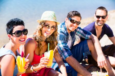 four friends sitting on lake beach