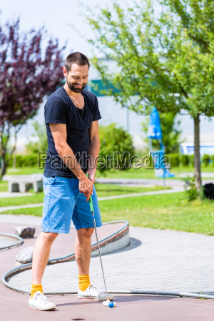 man playing miniature golf
