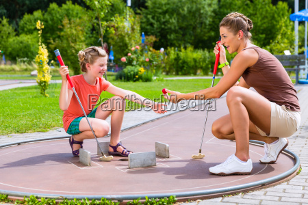 family playing miniature golf in summer