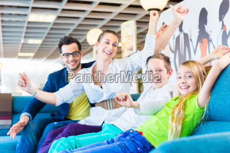 family buying couch in furniture store