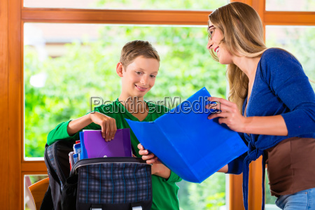 mother and son packing school bag