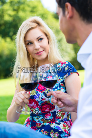 couple drinking red wine on grass