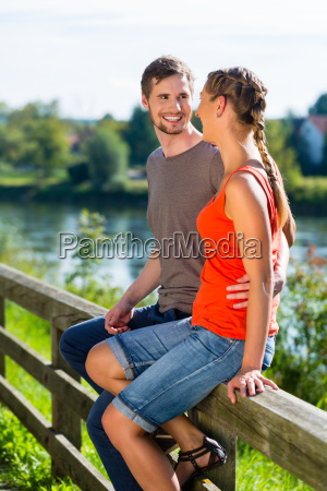 couple sitting at riverbank in summer