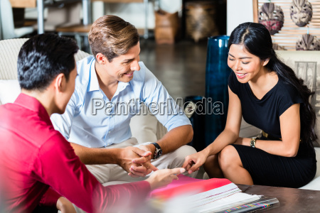 couple with salesman in furniture store