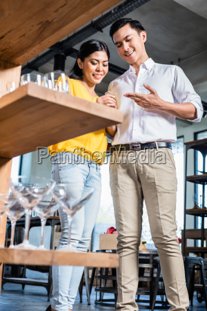 couple in furniture store choosing glasses