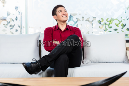 asian man sitting on sofa in