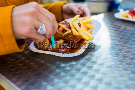 woman eating german currywurst at stand