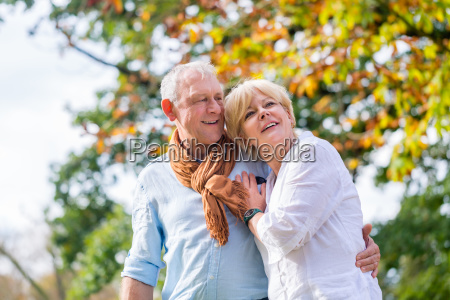 senior man and woman embracing each