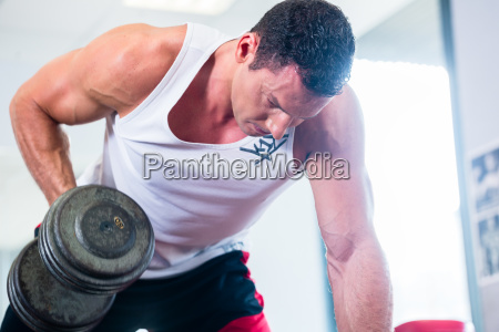 man with dumbbells at sport in