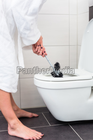 woman cleaning toilet using loo brush