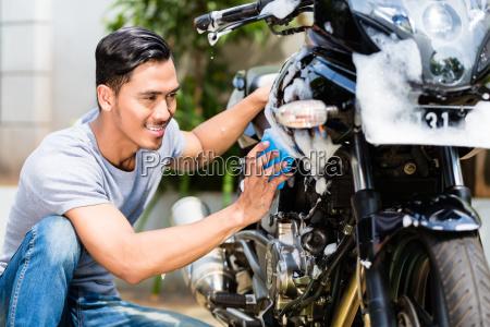 asian man washing his motorcycle or