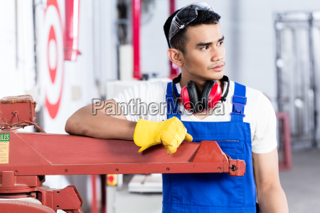 asian carpenter with electric saw in