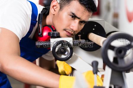 worker adjusting turning machine in factory