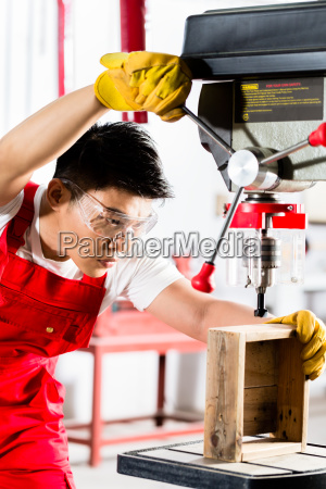 chinese man working with drill in