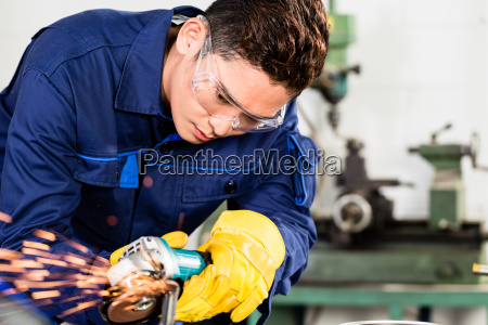 asian worker grinding metal in manufacturing