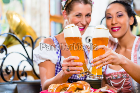 women in bavarian pub toasting with