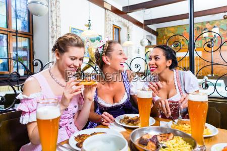 women in bavarian restaurant eating food