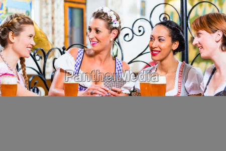 women in bavarian pub playing cards