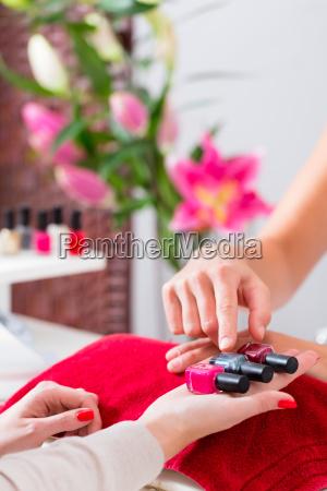 woman choosing nail polish in beauty