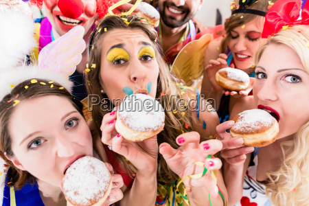 carnival party people eating donuts