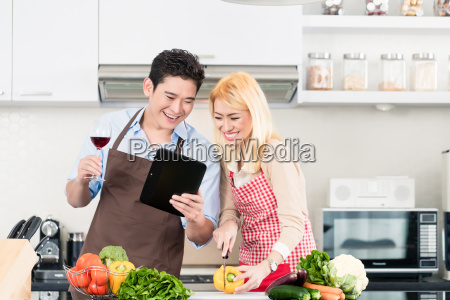 asian couple cooking after recipes from