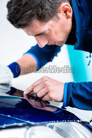 hard working man polishing car with