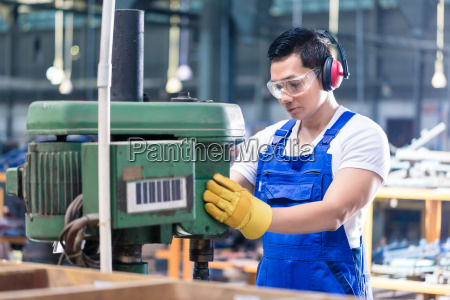 asian worker in factory on drilling