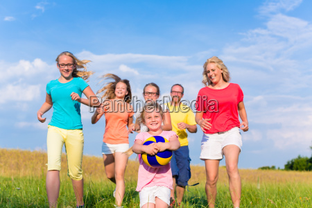 family playing ball games on meadow