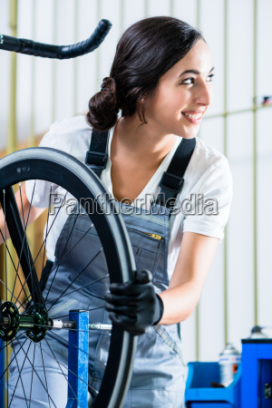 woman bike mechanic working on bicycle