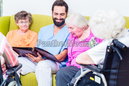 geriatric nurse looking at pictures with
