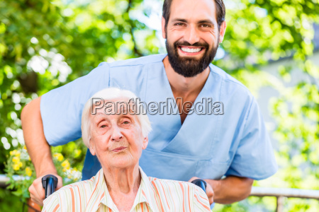 geriatric nurse pushing senior lady in