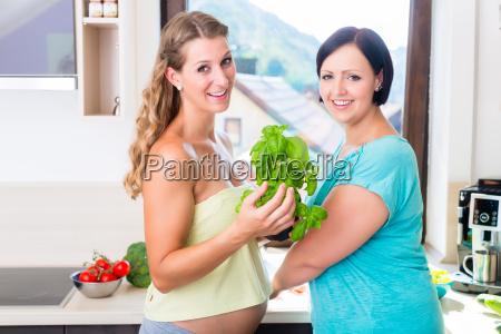 two pregnant best friends preparing healthy