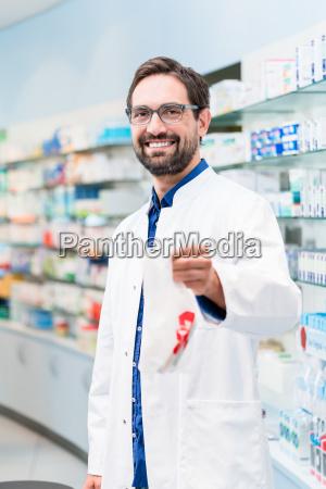 pharmacist in pharmacy selling pharmaceuticals in
