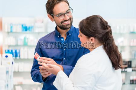 pharmacist talking to customer in drug