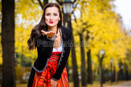 girl in dirndl blows a kiss